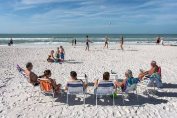 6 adults sitting in beach chairs on the beach